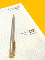 Image showing first January on a diary with pen on isolated color background with fine clipping path.